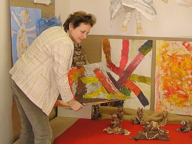Jindřiška Riedlová, ředitelka lounské umělecké školy, instaluje exponáty.