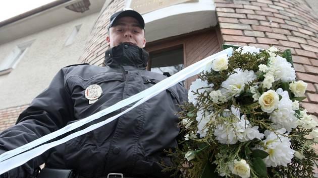 Strážník pokládá květiny k rodnému domu Otakara Jaroše v Lounech.