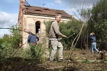 Dobrovolníci odstraňují náletové dřeviny z hřbitova u kostela v Přibenicích.