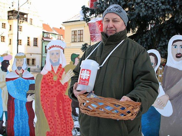 Martin Batala se zapečetěnou kasičkou a ošatkou u lounského vánočního stromu.