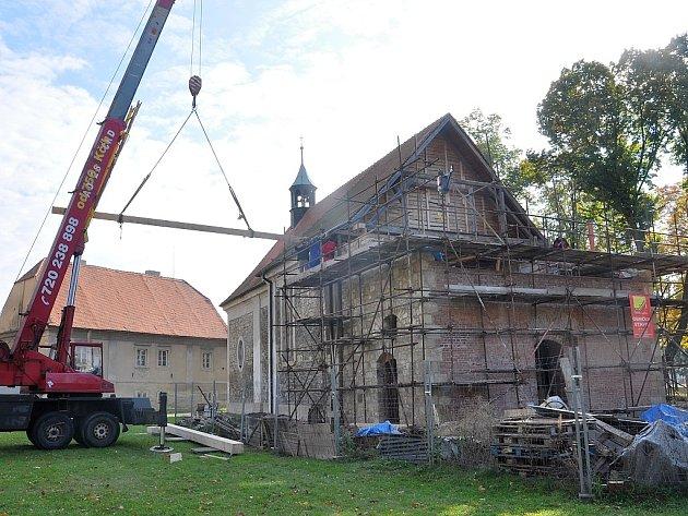 Jeřáb zvedá dřevěné trámy na strop nové věže kostela v Lenešicích na archivním snímku z roku 2012. Čtyři roky předtím věž kostela spadla.