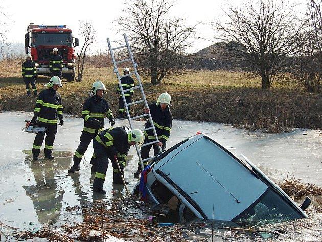 Hasiči vytahují auto ze staňkovického rybníka
