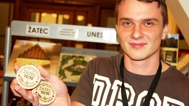 Martin Veselý z žateckého infocentra ukazuje nové výroční turistické známky pro sběratele, které připomínají 1010 let od první písemné zmínky o Žatci.