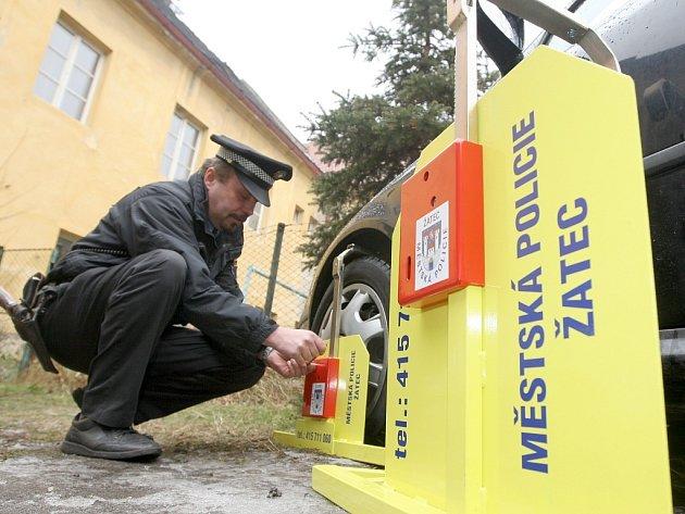 Městský strážník Pavel Klíma při instalaci blokovací botičky na jedno z nesprávně zaparkovaných vozidel.