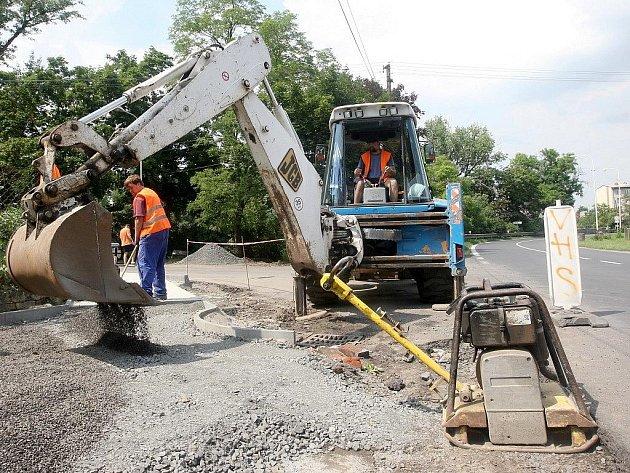Dělníci pracují na stavbě autobusových zastávek a chodníků na průtahu silnice I/27 Most – Plzeň v Radíčevsi u Žatce.