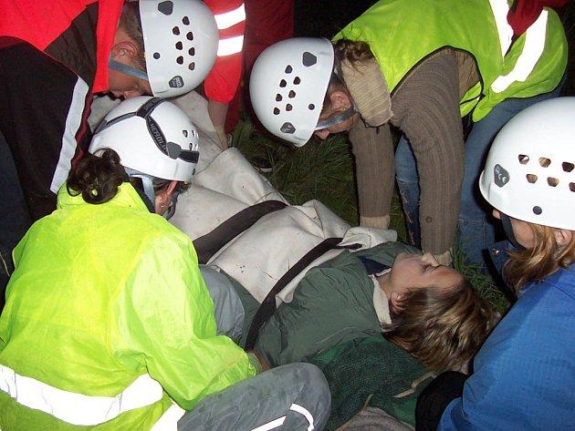 Dobrovolní záchranáři transportují pacienta s fixovanou nohou ve vakuové dlaze při cvičení u Perče.