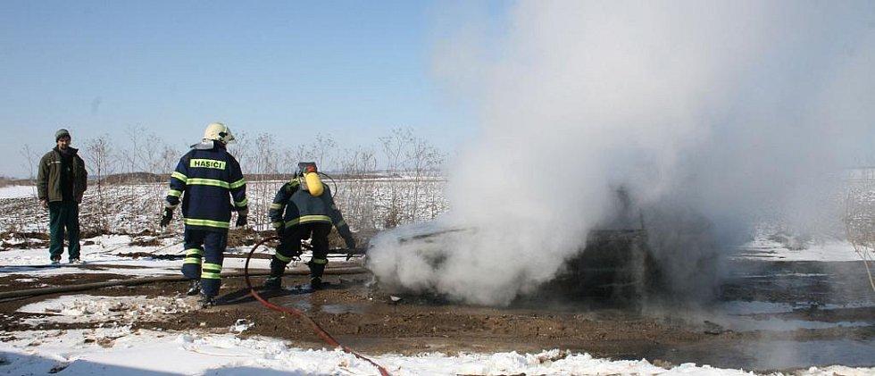 Hasiči likvidují požár vozidla.