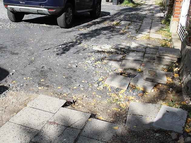 Rozbitý povrch v ulici Bří Čapků. Od léta se tam nepracuje, teprve nyní by se měly rozeběhnout práce na rekonstrukcích vozovky a chodníků. Stejně jako v Lidické a Dukelské ulici.
