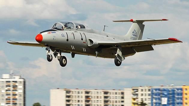 Letadlo L29 Delfín přistává v Čeradicích srazu, v pozadí je sídliště Žatec – Jih.