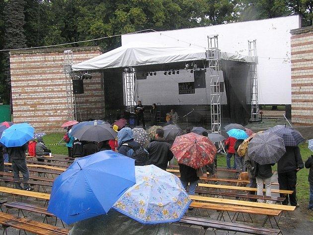 Lidé pod deštníky sledují vystoupení folkové kapely v amfiteátru bývalého letního kina během víkendového Vábení.