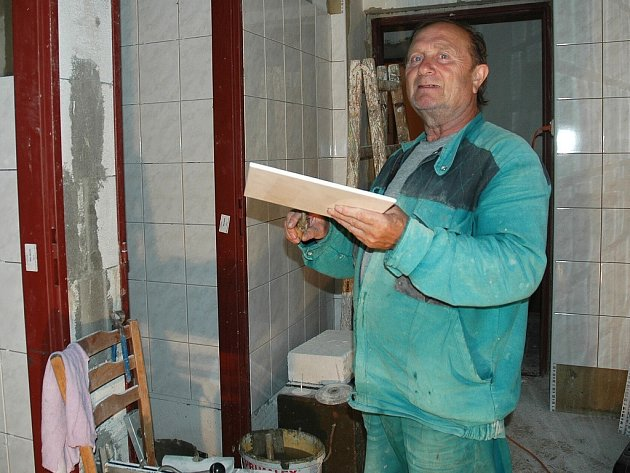 Jan Hlavsa lepí obkladačky na sociálním zařízení v azylovém domě v Libočanech, který prochází rekonstrukcí.