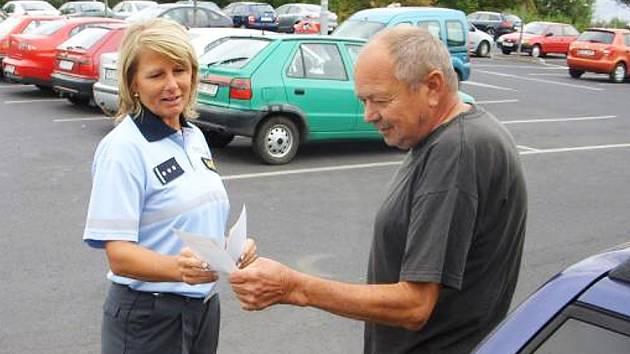 Jaromíra Střelcová z preventivně informační skupiny Policie ČR v Lounech vysvětluje řidičovi, jak správně zabezpečit auto na parkovišti u supermarketu.