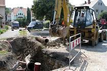 Bagrista pracuje na výkopu pro kanalizaci v centru Tuchořic. Dopravu tam kvůli tomu řídí semafory.