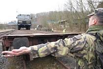 Rotmistr Antonín Holub navádí Tatru T 815 na vagon na nádraží v Trnovanech.