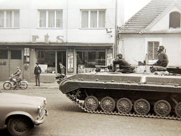 Tank projíždí kolem prodejny Radio televizních služeb v dnešní lounské ulici Husova. Za zády fotografa byla ještě nedávno policejní služebna.