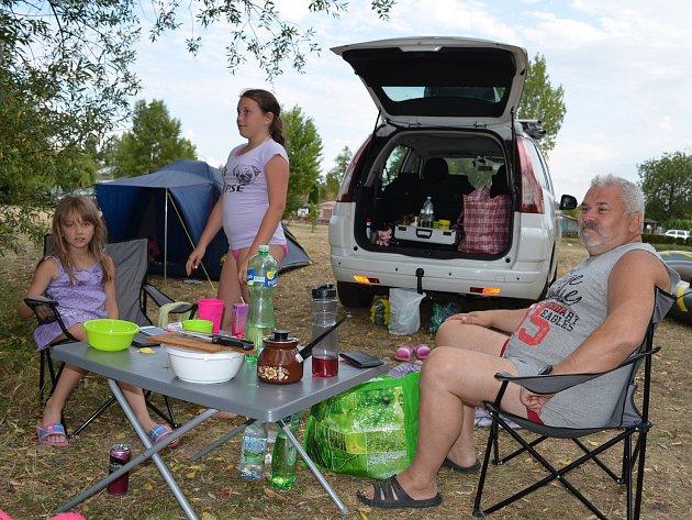 Stanování je pořád oblíbeným způsobem, jak trávit dovolenou. Na Nechranické přehradě v kempu U Hráze je spokojený Zdeněk Kuneš se svými vnučkami.