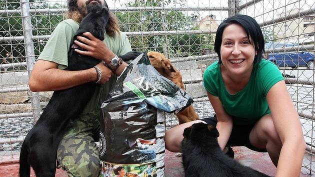 Redaktorka Deníku Mirka Strnadová a provozovatel útulku pro zvířata David Kubalík předávají pytel granulí psům v Jimlíně.
