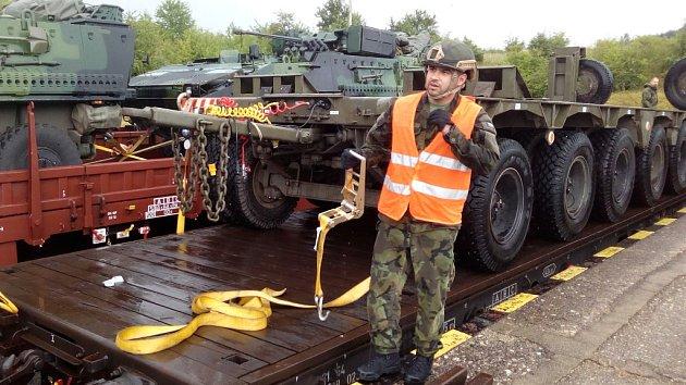 Vojáci nakládají techniku na železniční vagóny