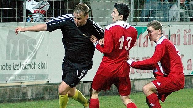 Fotbalové utkání Blšan (v tmavém) proti Lounům. Horst Siegl st obchází Slušného a Lazarika