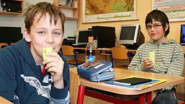 Žáci základní školy v Zeměchách Michal Husinecký (vlevo) a Vojtěch Krejčík jí o přestávce okurky. Zeleninu a ovoce tam dostávají dvakrát týdne.