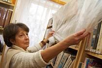 Ředitelka Jitka Martinovská přikrývá knihy igelitem
