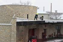 Hasiči shazují sníh ze střechy autobusového nádraží v Žatci