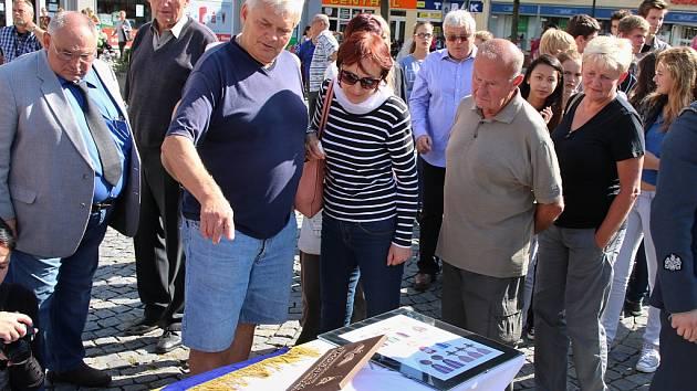 Lidé si prohlížejí nové pamětní desky, které budou už za pár dnů instalovány na rodné domy letců.