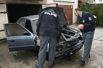Policisté obhlížejí ohořelý automobil