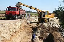 Dělníci pracují na zpevnění svahu s komunikací u Staňkovic