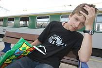 Mladík čeká na nádraží při stávkovém přerušení vlakové dopravy.
