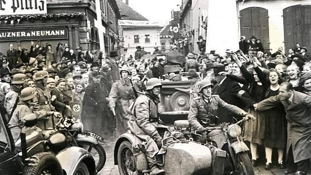 Wehrmacht vjíždí 9. října 1938 na náměstí z dnešní Jiráskovy ulice. Na snímku je patrné, že němečtí vojáci byli v Žatci nadšeně vítáni.