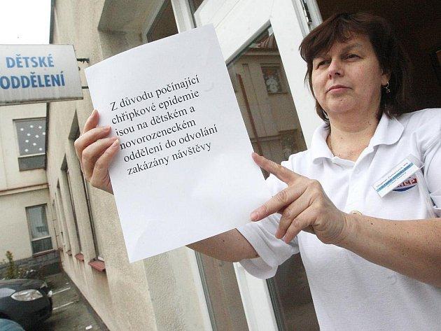 Vrchní sestra nemocnice v Žatci Dagmar Zemanová připevňuje cedulky se zákazem vstupu pro návštěvy.