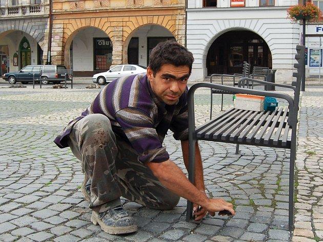 Marek Tóth připevňuje zpět lavičky na žateckém náměstí Svobody.