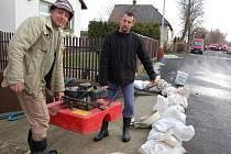 Miroslav Kettner (vlevo) a Petr Jánský připravují čerpadlo při povodni v Oboře na Lounsku.