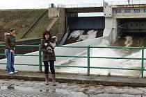 Lidé sledují odtok vody z přepadu hráze na Nechranicích