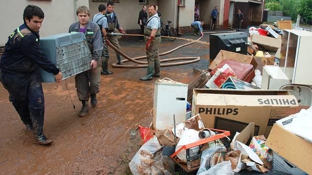 Dobrovolní hasiči z Krásného Dvora uklízejí po bleskové povodni v Kryrech. Do městečka přijeli rovnou z jiných povodní, pomáhali na Litoměřicku.
