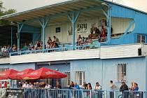 Diváci sledují hru na tribuně fotbalového stadionu v Lounech. Stav zázemí i tribuny už není vyhovující,  v Lounech se příští rok zřejmě začne připravovat rekonstrukce.