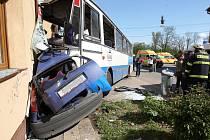 Autobus přimáčkl ke zdi rodinného domu osobní vůz.
