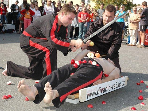 Matěj Ježek samurajským mečem přesekává jablka na břichu Martina Horáčka, pomáhá mu Šimon Pečenka.