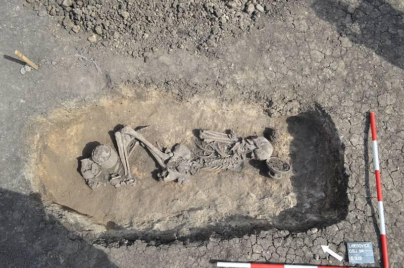 Kolmý snímek hrobu sněkolika nádobami přiloženými jako milodary.