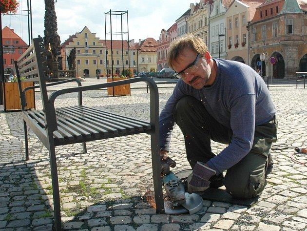Milan Štigler odřezává železnou lavičku z plochy žateckého náměstí.