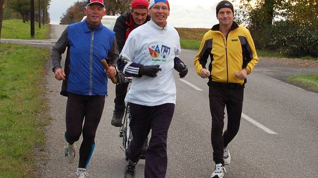 Skupinka běžců se blíží k Žatci, kolem Nového Sedla je vede Roman Daniš.