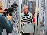 Josef Šimonovský, předseda okrskové volební komise v Novém Sedle, nese urnu do věznice. Natáčela tam Česká televize.