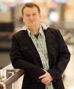 V zelenomodré kárované košili s černým sakem