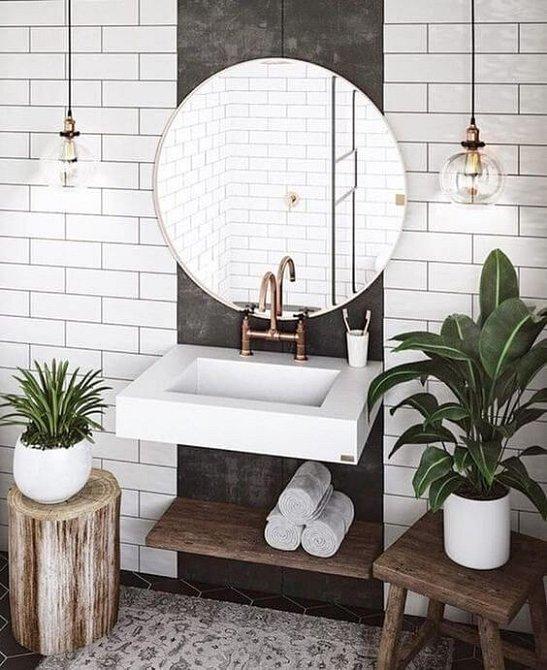 Nesmrtelná kombinace - bílý obklad, dřevo, kulaté zrcadlo a květiny.