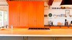 Druhá část kuchyně je vymalována do oranžové barvy.
