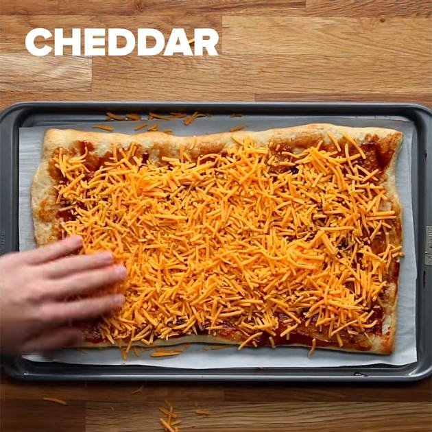 Na upečené těsto nastříkejte trochu BBQ omáčky (nebo tu, co máte radši) a rozetřete ji po něm. Posypejte sýrem cheddar.