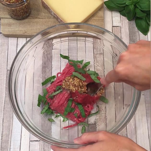 V misce míchejte mleté hovězí, rajčatový protlak, nakrájenou bazalku a dochuťte hořčicí, pepřem a solí.