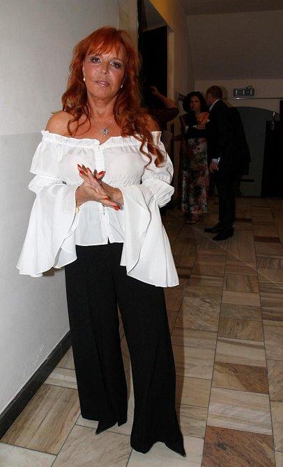 Olalá! Tak tohle je model! Netradiční, letní a slušivý! Marcela jednoduché černé kalhoty ze splývavého materiálu doplnila o nepřehlédnutelnou bílou halenku obepínající ramena. Vypadá skvostně, že?