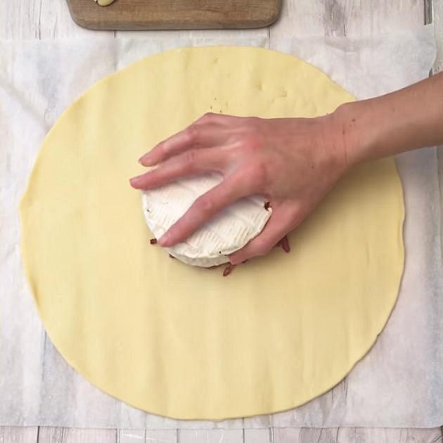 Na pánvi si osmahněte slaninu. Nasypte ji doprostřed listového těsta a dejte na ni vrškem dolů camembert s česnekem.